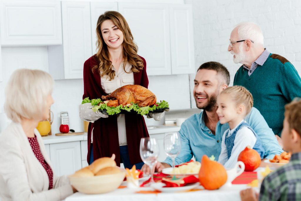 beautiful smiling woman carrying baked turkey for thanksgiving dinner with family