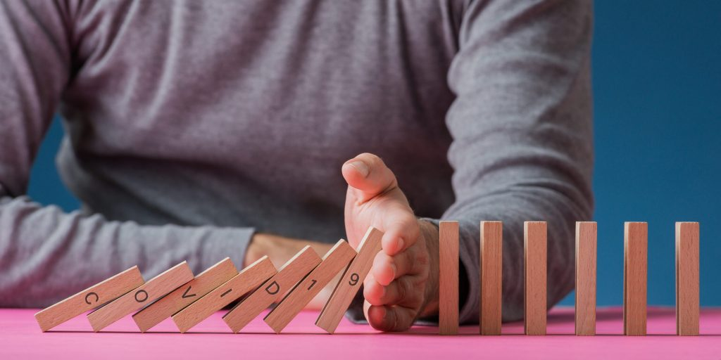 Conceptual image of preventing new coronavirus Covid 19 disease to spread widely - man stopping falling dominos with his hand.