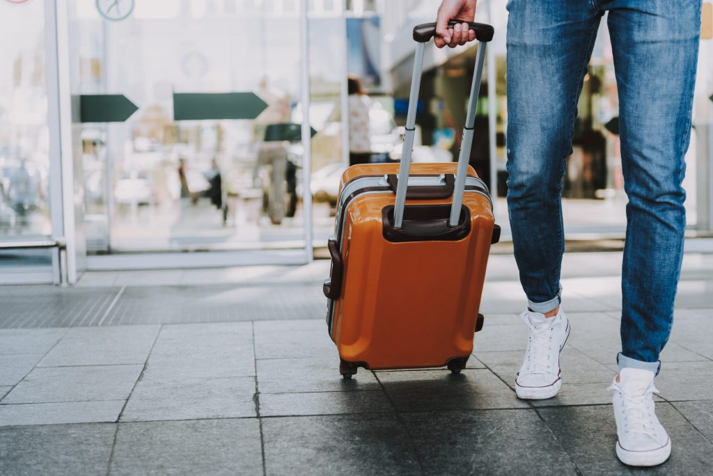 Close-up of man walking with suitcase. He is going in departure lounge. Copy space in left side