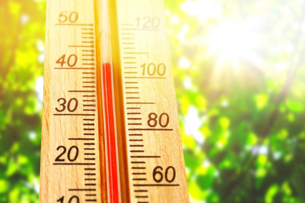 Thermometer displaying high 40 degree hot temperatures in sun summer day